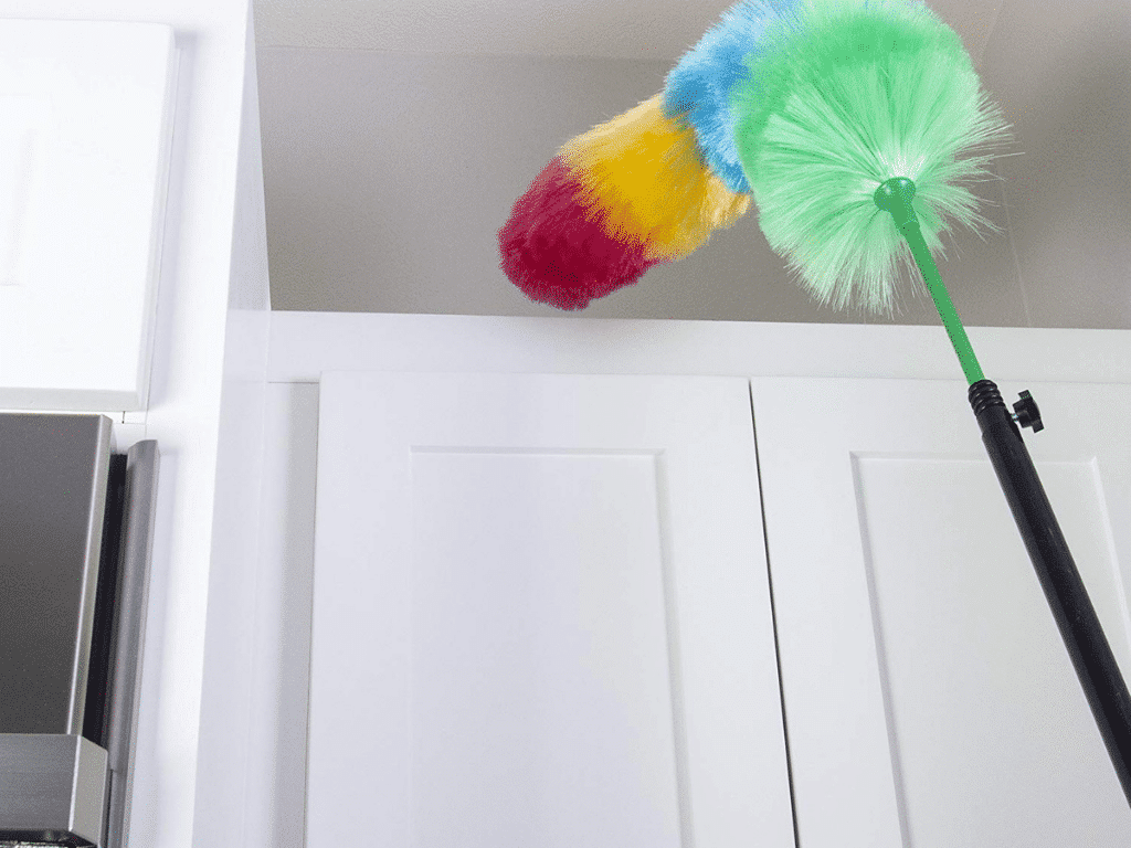 imagine of Image of Kitchen + Home Large Static Duster with Bonus Extension Pole dusting top of cabinet