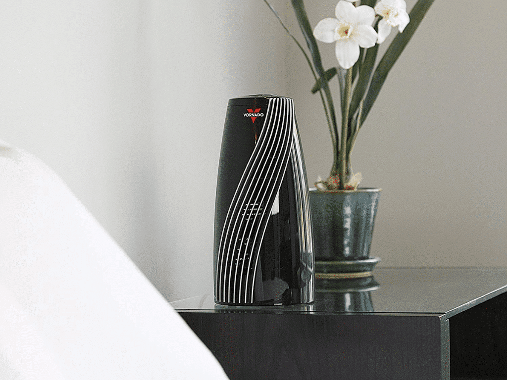 Staged image of Vornado SRTH Small Room Tower Heater on table beside flowers