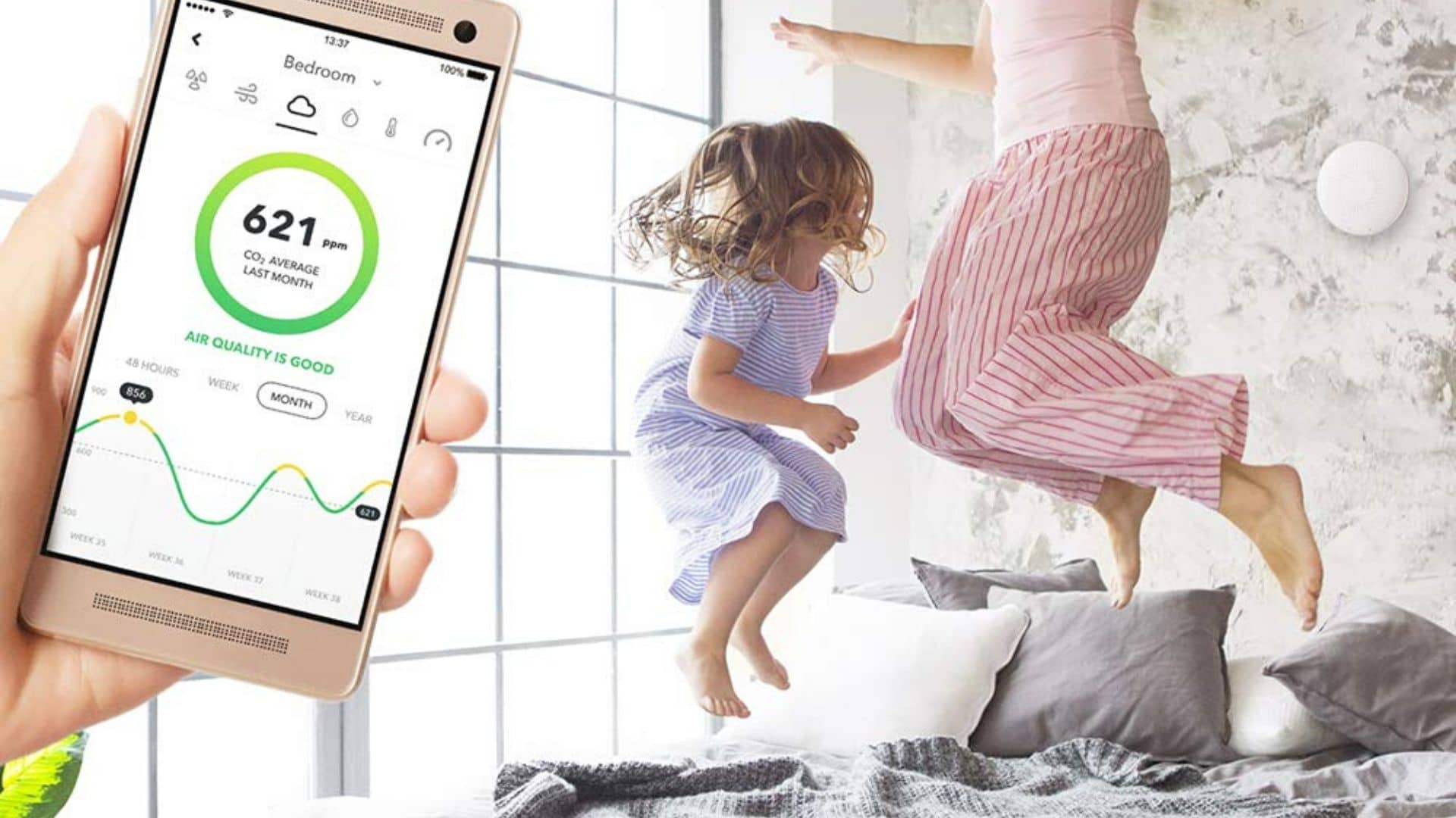 image of person holding phone with airthings mobile app while girl jumps on bed