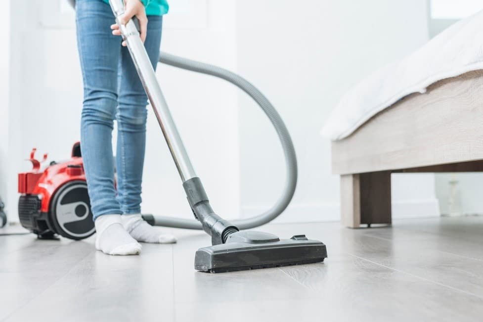 Image of person vacuuming floor