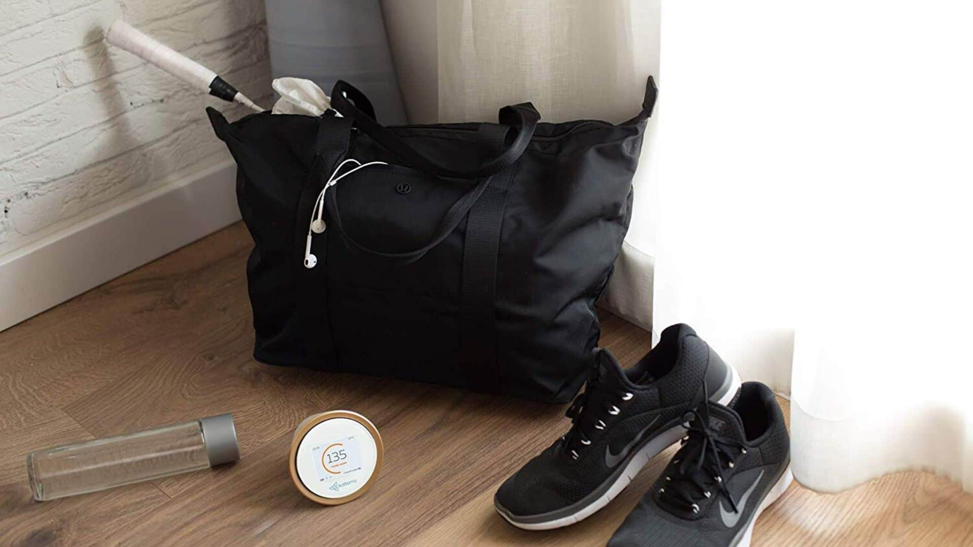Picture of Kaiterra Laser Egg+ Chemical: Indoor Air Quality Monitor beside black gym bag and shoes