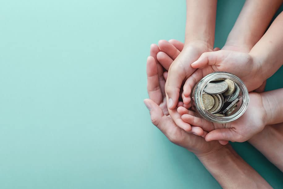 A picture of hands overlapping holding a glass jar with change in it.