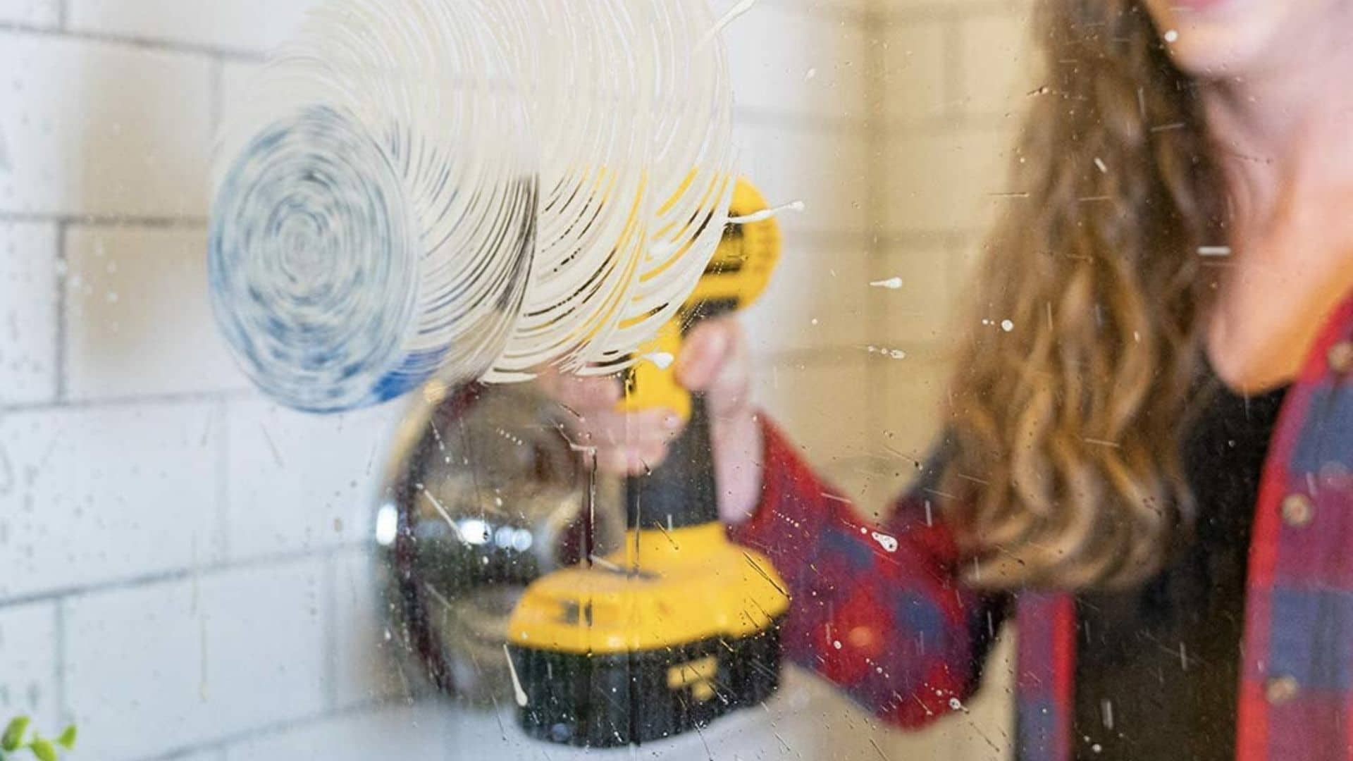 picture of woman using rotoscrub bathroom cleaning brush drill to wash shower glass