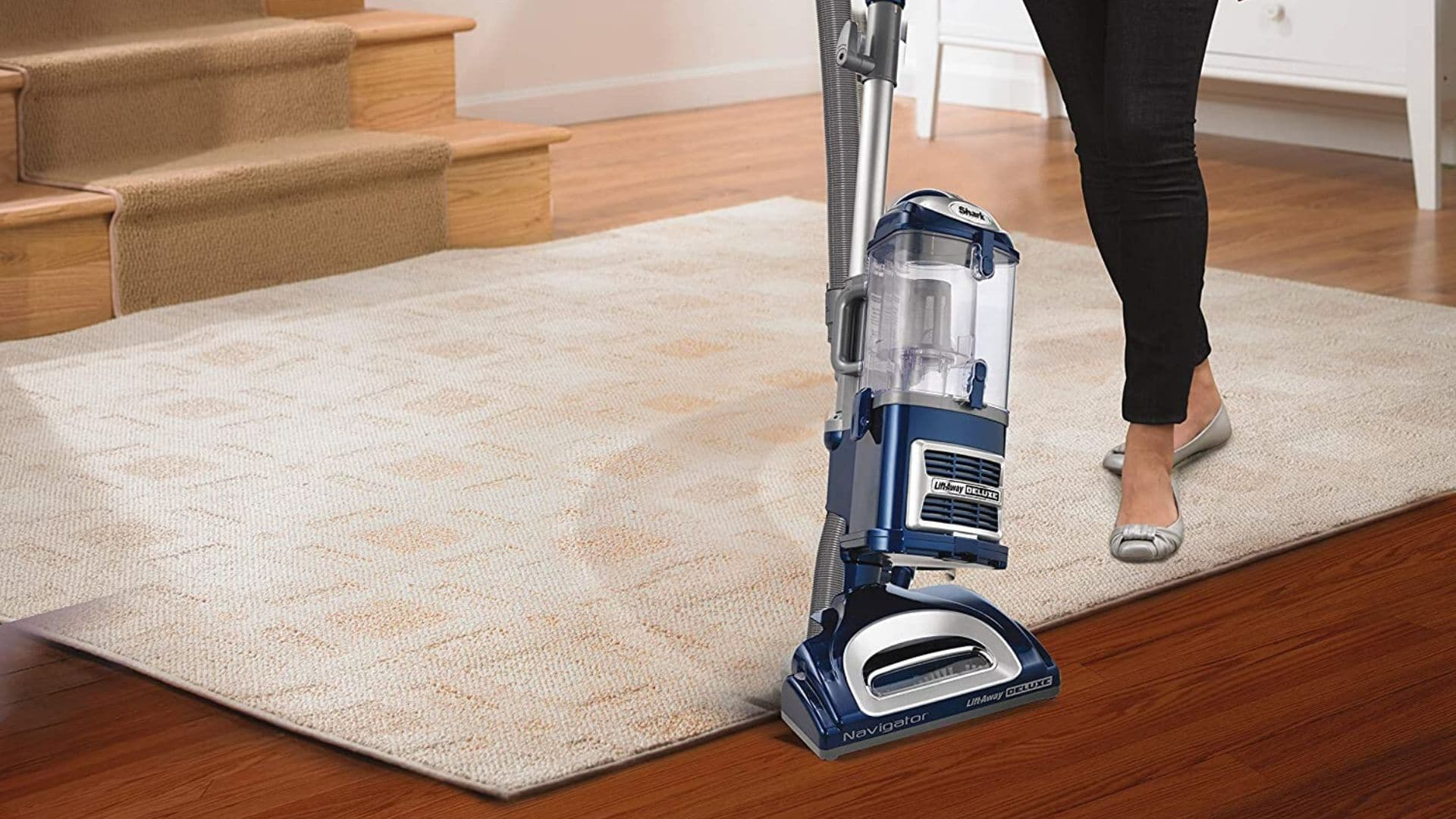 picture of woman using the shark navigator lift away deluxe nv360 upright vacuum cleaner upholstery tool to clean carpet and hard wood floor