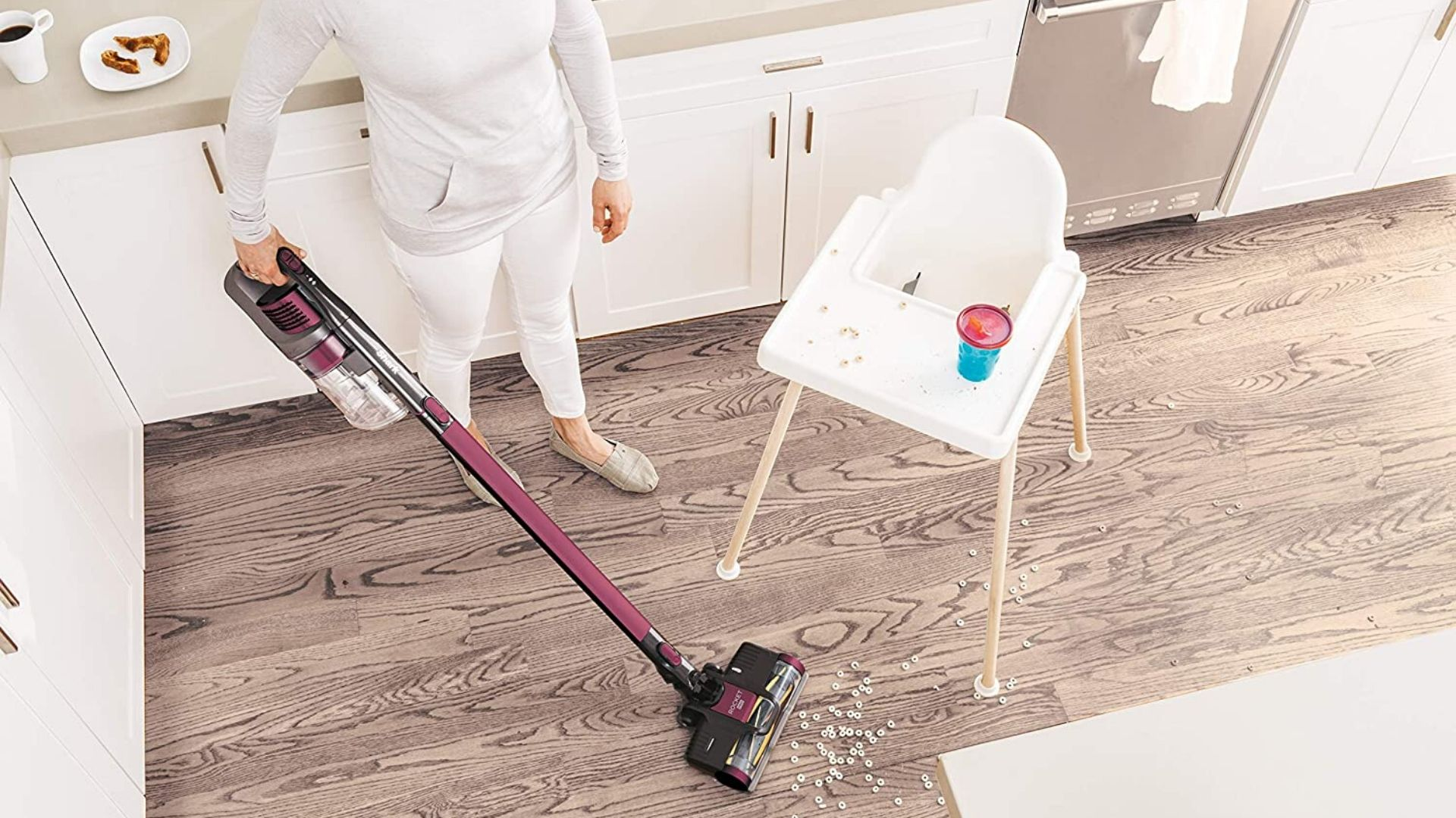 image of woman using shark rocket pet pro to clean cereal off of kitchen floor