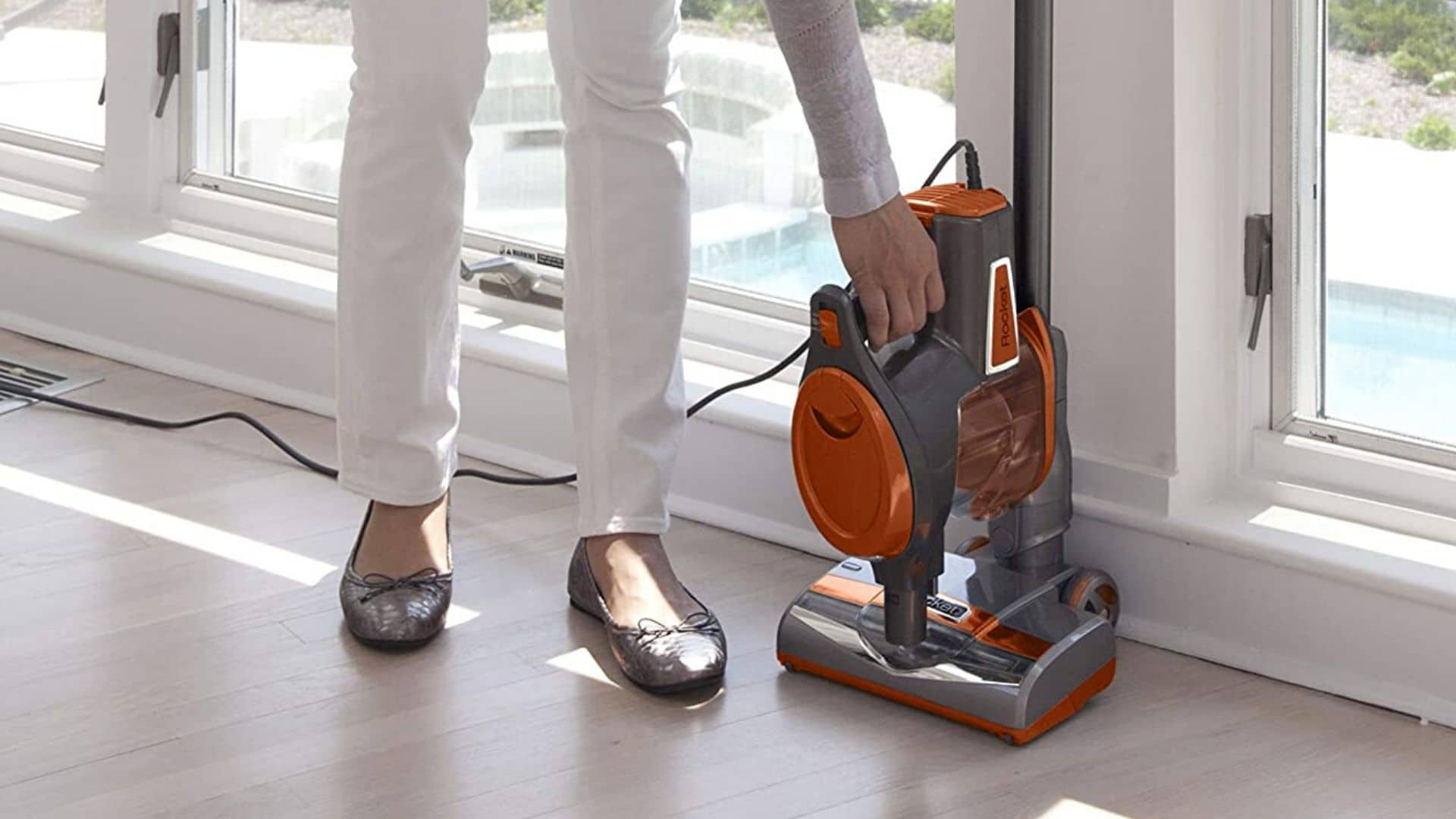 image of woman removing hand vacuum from shark rocket ultra light corded bagless vacuum HV301