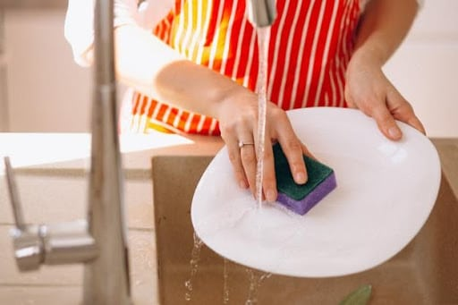 Image of a person cleaning a dish using a sponge in a sink