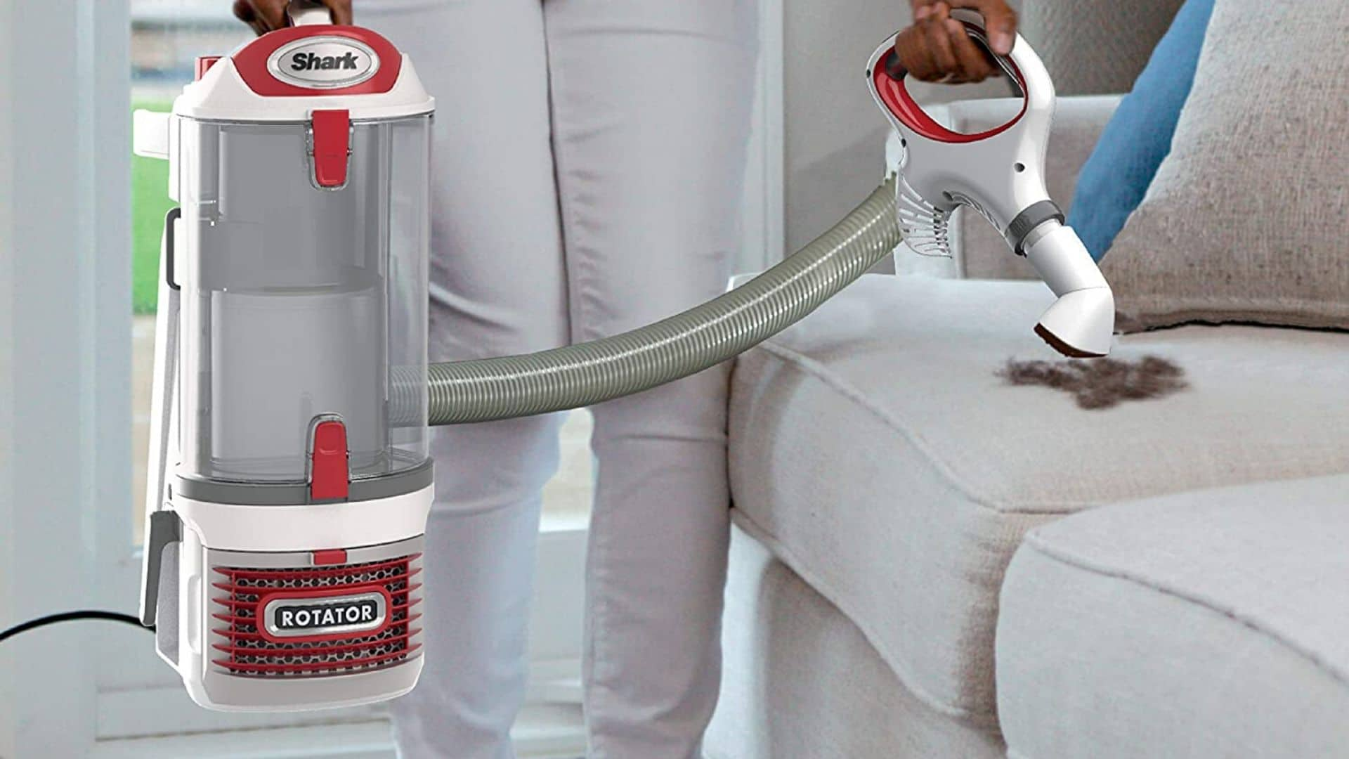 picture of woman using shark upright corded bagless vacuum for carpet and hard floor to vacuum a couch