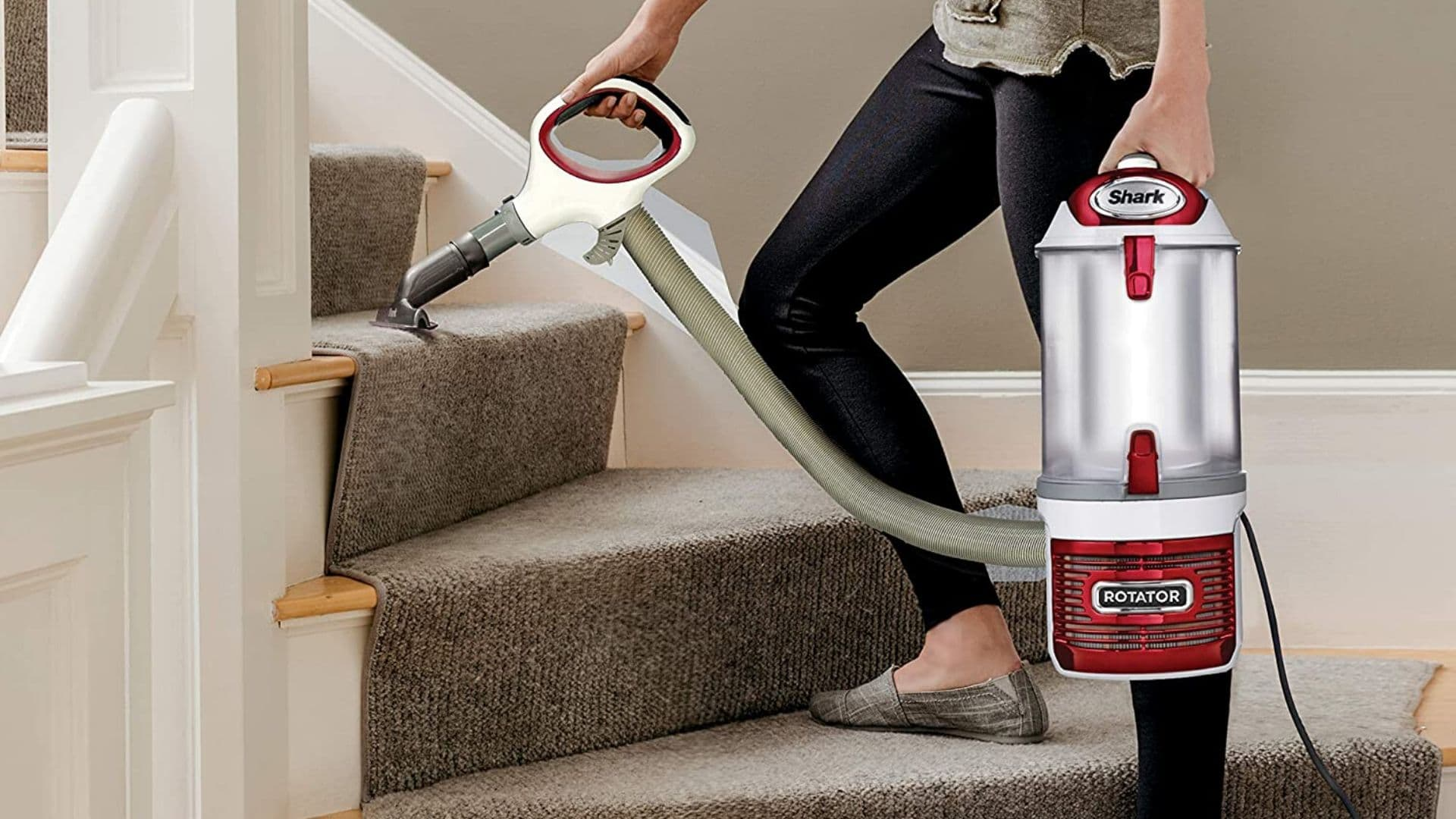 woman using upright corded bagless vacuum to clean stairs