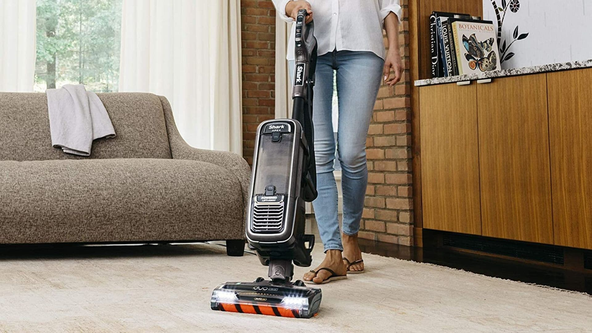 image of woman using Shark APEX Upright Vacuum with DuoClean for Carpet and HardFloor Cleaning, Zero-M Anti-Hair Wrap, & Powered Lift-Away with Hand Vacuum (AZ1002) to clean carpeted floor