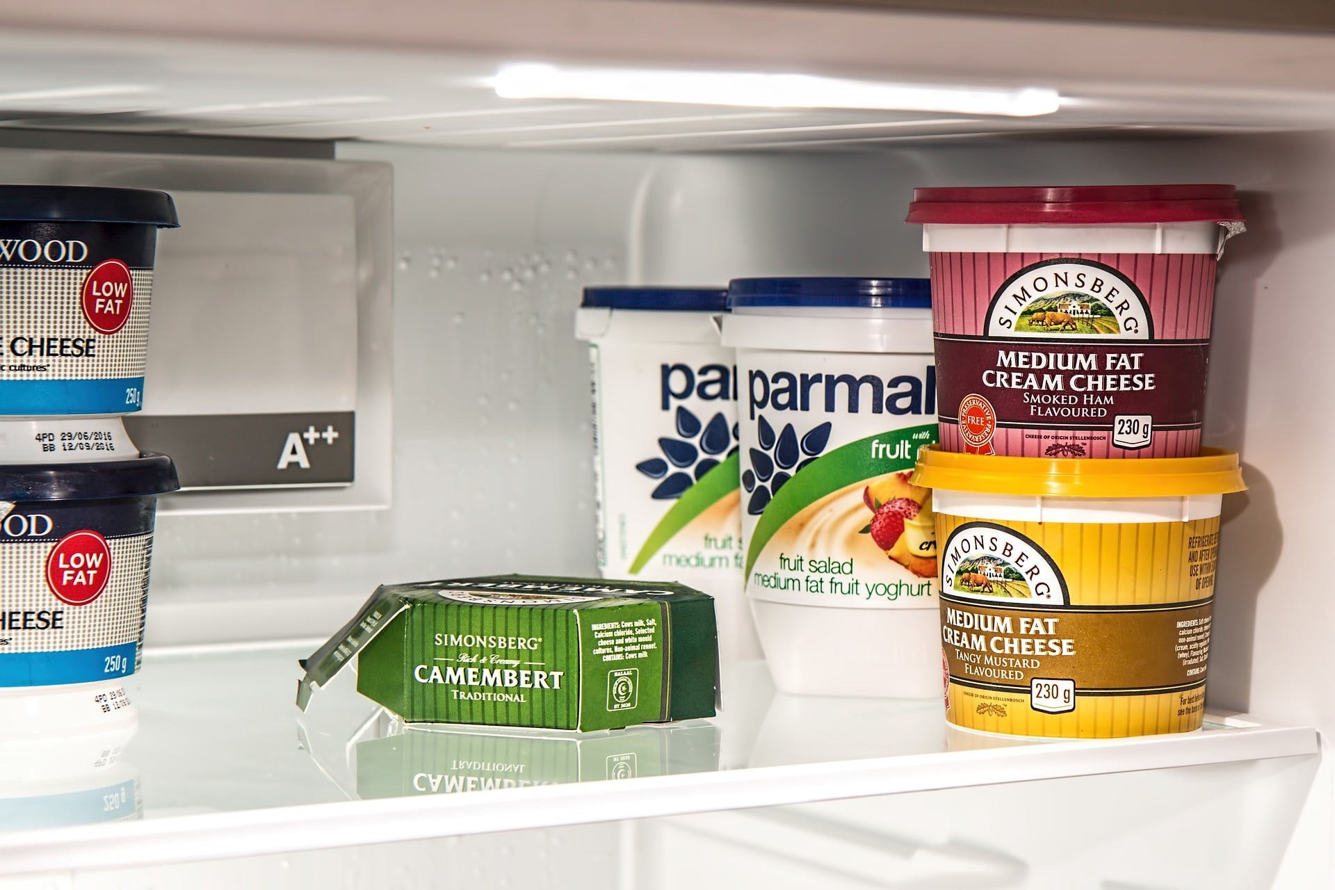 picture of yogurt, cheese, and cream cheese in fridge